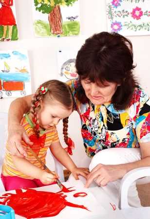 Child with teacher draw paints in playroom. Preschool. Stock Photo - 6443838