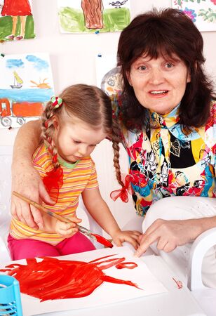 Child with teacher draw paints in playroom. Preschool. Stock Photo - 6443967