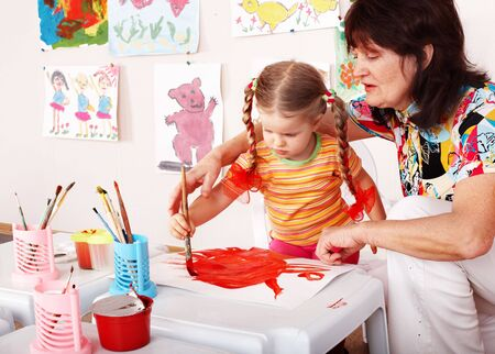 Child with teacher draw paints in playroom. Preschool. Stock Photo - 6443959