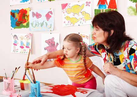 Child with teacher draw paints in playroom. Preschool. Stock Photo - 6443962