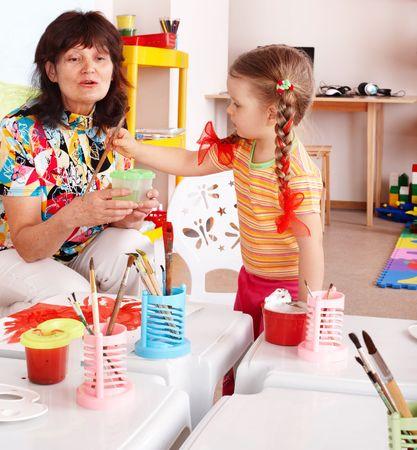 playroom: Ni�o con profesor dibujar pinturas en la sala de juego. Preescolar.