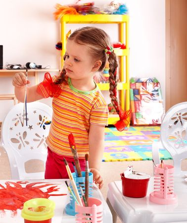 Child with paint and brush in playroom. Preschool. photo