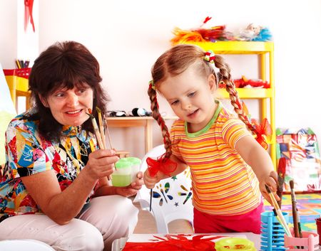 Child with teacher draw paints in playroom. Preschool. photo