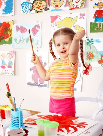 Child with picture and brush in playroom. Preschool. photo