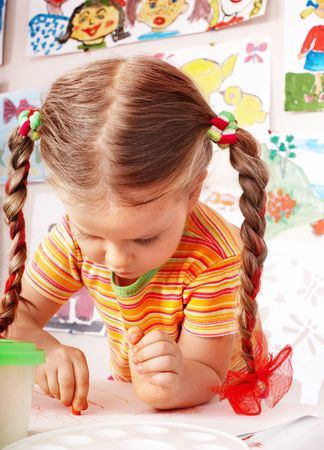 Child with piece of chalk draw  in playroom. Preschool. photo