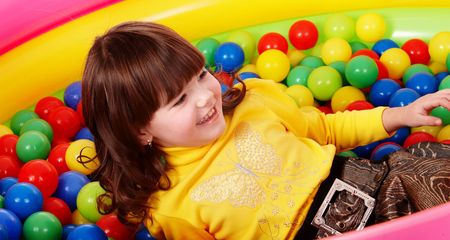 playcentre: Preschooler girl with ball in play room. Childcare. Stock Photo