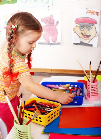 daycare: Child  prescooler with colour pencil in play room.