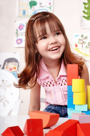 upbringing:  Child with wood  block and construction set in play room.  Preschool.