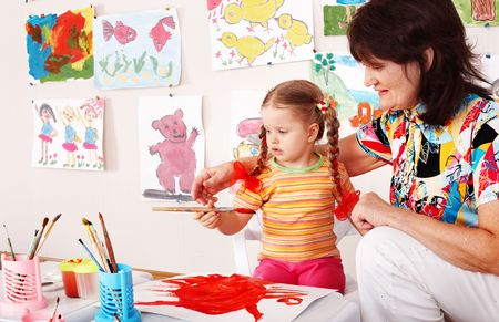 upbringing: Child with teacher draw paints in playroom. Preschool.