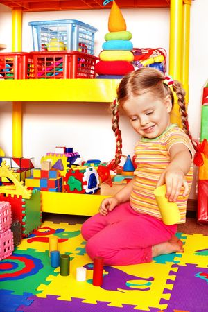 Child with puzzle, block and construction set in playroom. Preschool. photo