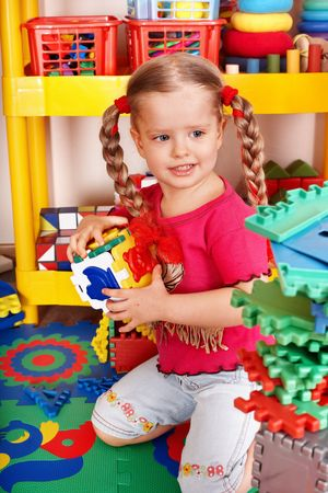 upbringing:  Child with puzzle, block and construction set in play room. Preschool.