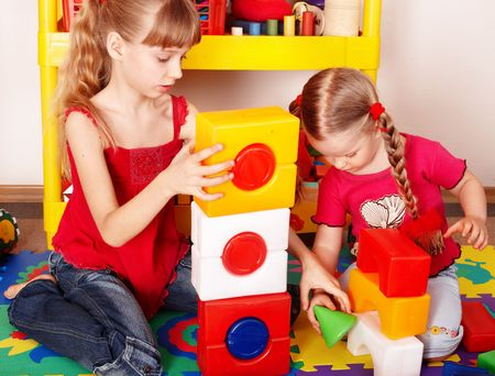 red centre:  Child with puzzle, block and construction set in play room. Preschool.