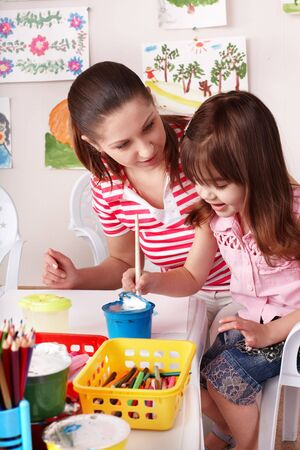Child with teacher draw paints in play room. Preschool.    photo