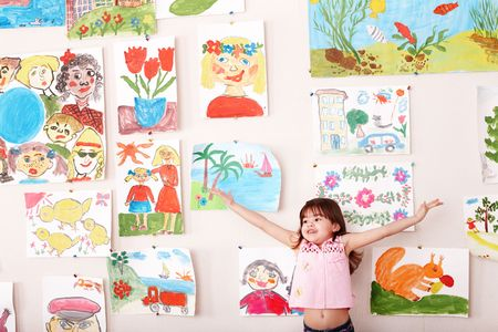 upbringing:  Child with hand up and picture  in playroom. Preschool. Stock Photo