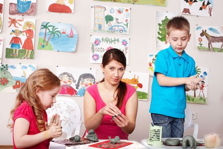 Group child and teacher mould from clay in play room. Preschool. photo