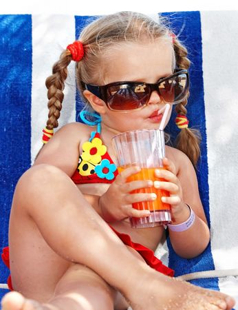 Child girl in glasses and red bikini drink juice. photo