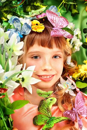 Beautiful girl with butterfly and flower on green grass. photo