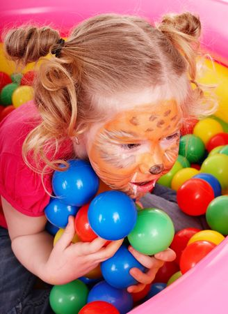 Little girl with paint on face  and group of  ball. Play room. photo