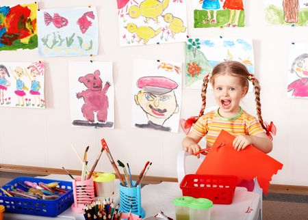 upbringing: Child with scissors cut paper in play room. Preschool. Stock Photo
