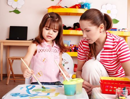 Child with teacher draw paints in play room. Preschooler. photo