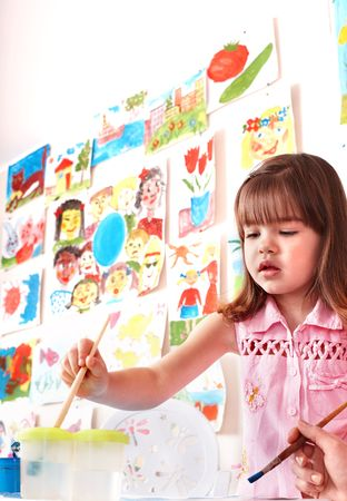 Child with picture and brush in play room. Preschool. photo