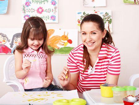 preschool: Child with teacher draw paints in play room. Preschooler.