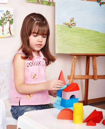 Child with wood block and construction set in play room. Preschool. photo