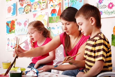 upbringing: Child with teacher draw paints in play room. Preschool..