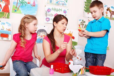 Children  with teacher  in play room. Preschooler. photo