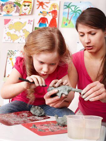 creativity artist:  Molde de ni�a de ni�o de arcilla en la sala de juego. Preescolar.