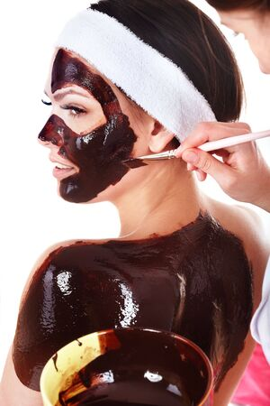 beauty parlour: Beautiful girl  having  chocolate facial mask apply by  beautician. Isolated.