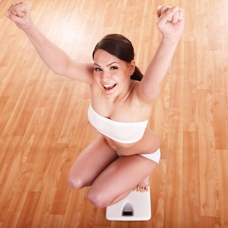 losing control: Happy beautiful girl on scales.  Weight-loss.