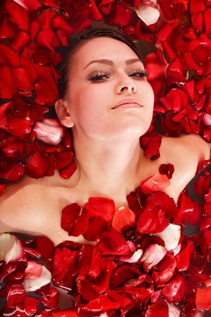 Beautiful girl in pool with rose petal. Body care. photo
