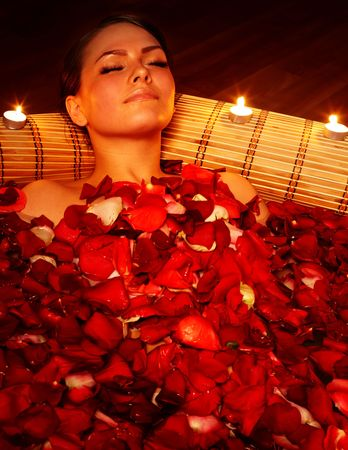 Beautiful girl in jacuzzi with rose petal and candle. Body care. photo