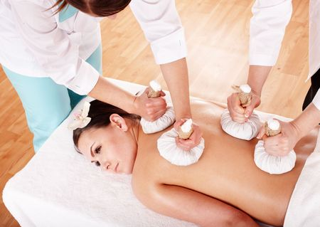 beauty parlour: Girl  having Thai herb compress massage in beauty spa. Body care.
