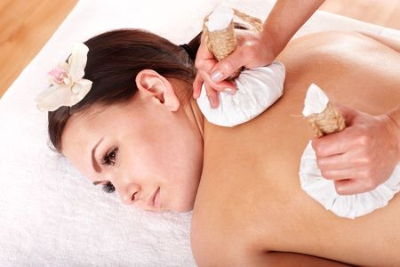 Girl  having Thai herb compress massage in beauty spa. Body care. photo