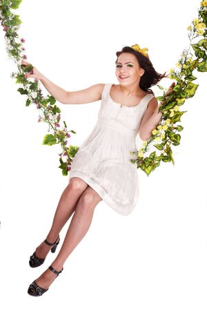 Beautiful girl in white dress swinging on flower swing. Isolated. photo