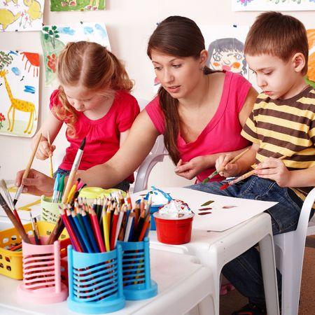 maestra jardinera: Ni�o con profesor dibujar pinturas en la sala de juego. Preescolar.