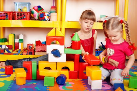 zone: Child with puzzle, block and construction set in play room. Preschool.
