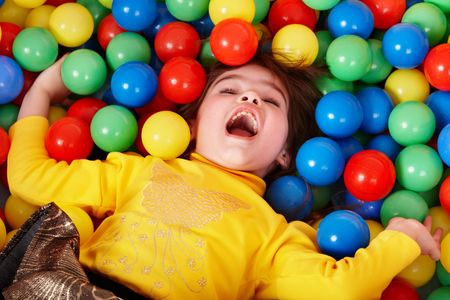 playcentre:  Happy little girl in group colorful ball.