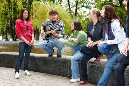 Group of people in city park listen music.Outdoor. photo