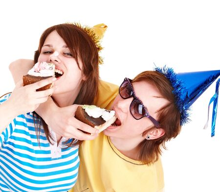 Man in party hat and girl eating cake. Isolated. photo