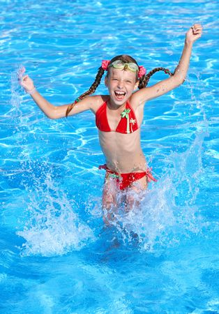 Girl with protective goggles and red swimsuit splashing in swimming pool.