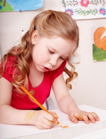 upbringing: Little girl with colour pencil draw in preschool.