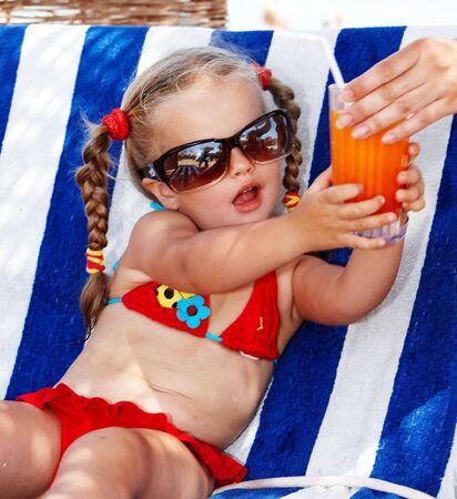 child bikini: Child girl in glasses and red bikini drink orange juice.