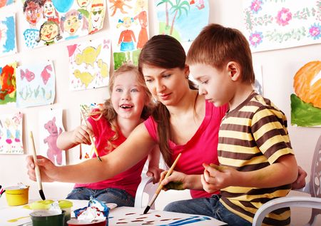 Children  with teacher draw paints in play room. Child care. photo