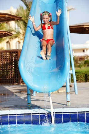 outdoor pursuit: Girl sliding down water slide. Summer.