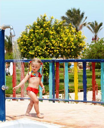 Child in red bikini take shower. Outdoor. photo