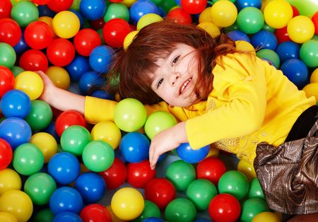 Happy little girl in group colourful ball. Stock Photo - 6964110