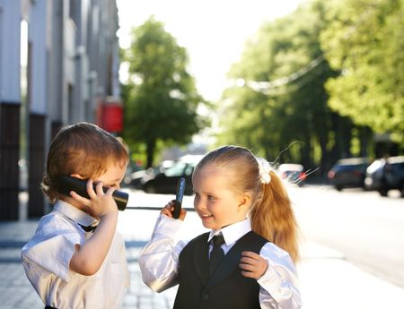 Children in business suit with mobile phone outdoors. Concept. photo